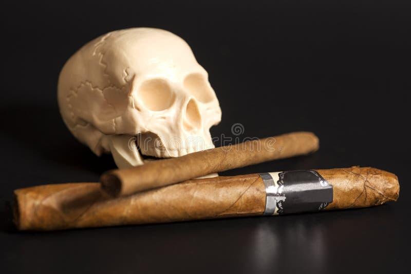 Cigarros que fuman de la acción humana del scull en negro foto de archivo libre de regalías