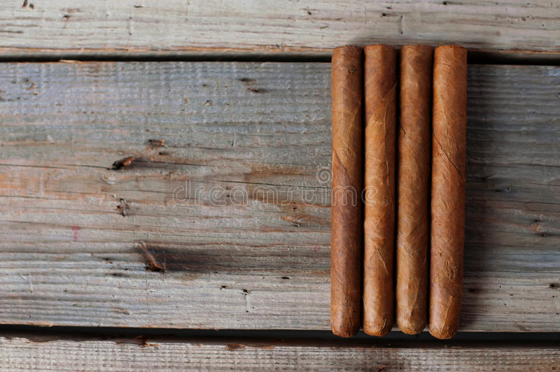 Cigars and cognac on an old wooden table royalty free stock image