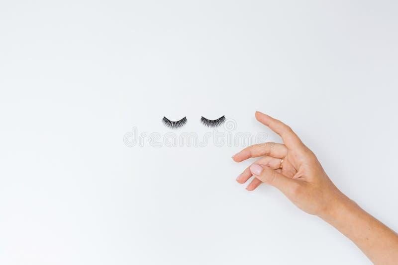 Cigli falsi e mano femminile che si trovano sul fondo bianco Bellezza e concetto di trucco Flatlay, modello, vista sopraelevata e fotografie stock libere da diritti