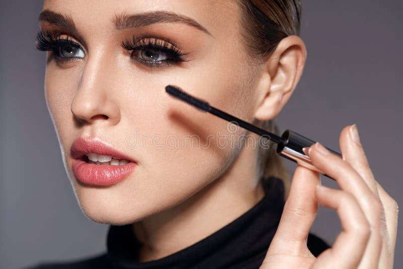 Cigli neri lunghi Donna con trucco che applica i cosmetici immagine stock