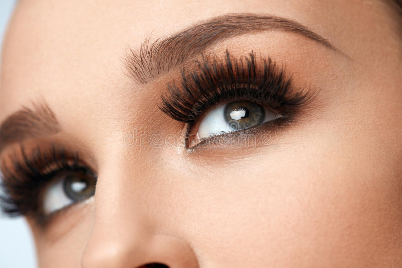 Cigli neri lunghi La bella femmina del primo piano osserva con trucco immagine stock