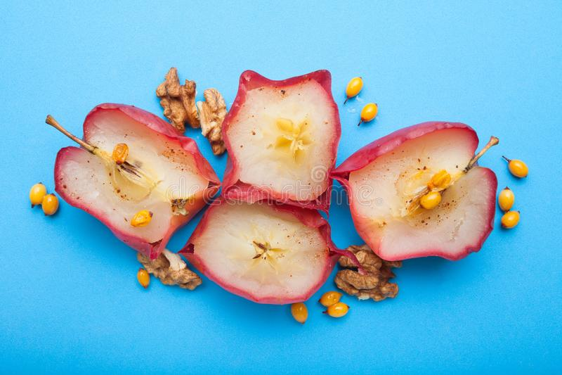 Ciie piec jabłka z pikantność i jagodami na błękitnym tle zdjęcia stock
