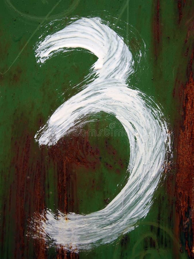 Cijfer drie wordt getrokken door een witte verf stock afbeeldingen