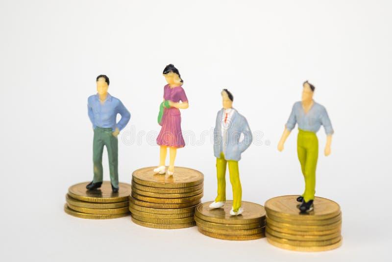 Cijfer miniatuurzakenman of kleine menseninvesteerder en beambtesecretaresse die zich op muntstukstapel bevinden, voor geld en fi stock foto