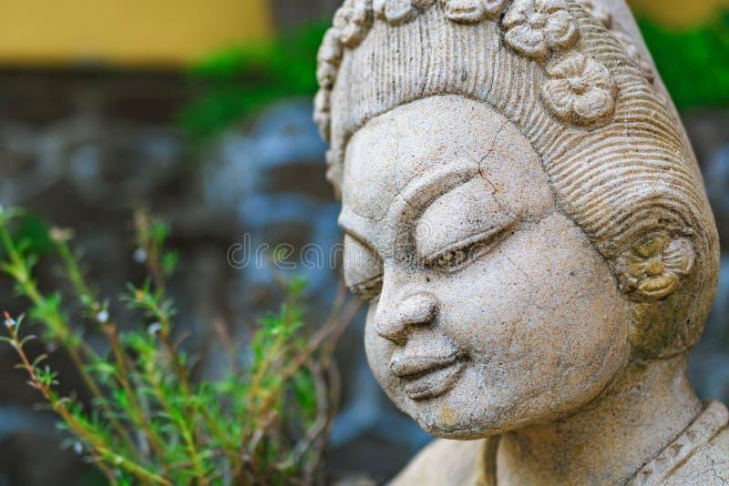 Cijfer van Aziatische deity van een steen in een stille tuin stock fotografie