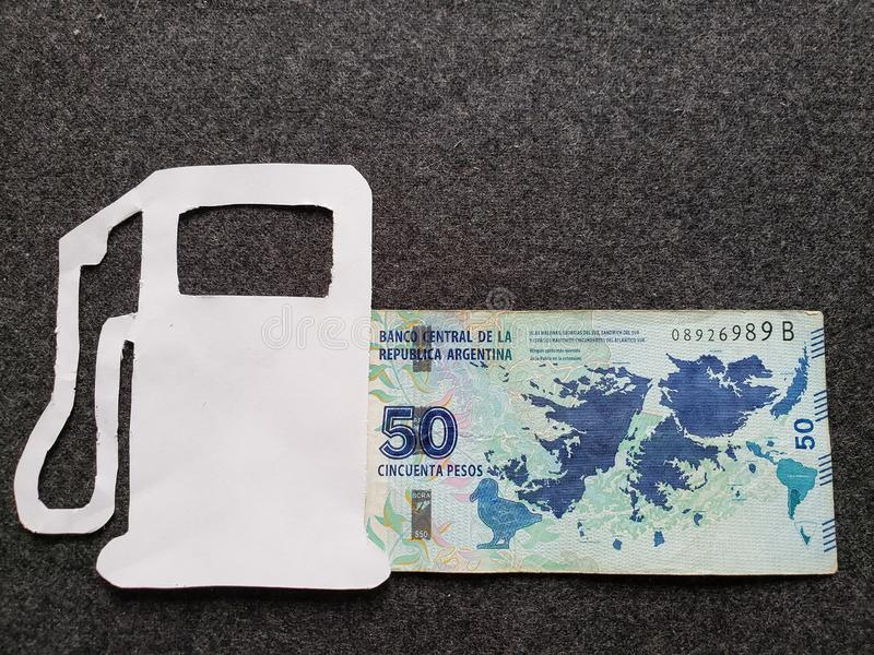 cijfer van benzinepomp in wit en een Argentijns bankbiljet van vijftig peso's stock foto