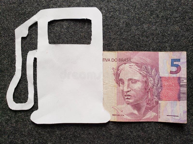 cijfer van benzinepomp in wit en een Braziliaans bankbiljet van vijf reais stock afbeeldingen