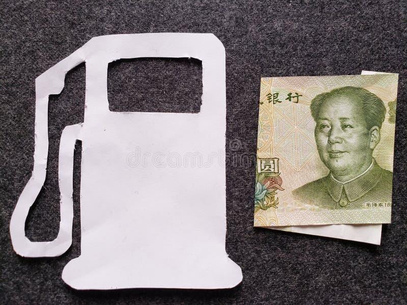 cijfer van benzinepomp in wit en een Chinees bankbiljet van één yuan royalty-vrije stock afbeelding