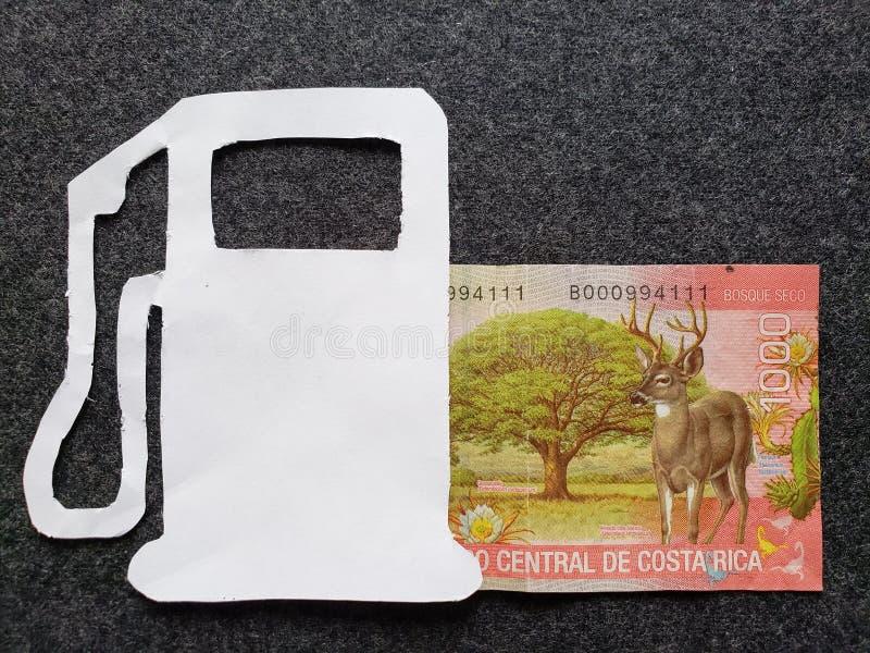 cijfer van benzinepomp in wit en een Costa Rican-bankbiljet van 1000 colones stock fotografie