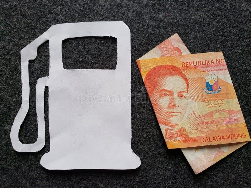 cijfer van benzinepomp in wit en een Filippijns bankbiljet van twintig peso's royalty-vrije stock foto's