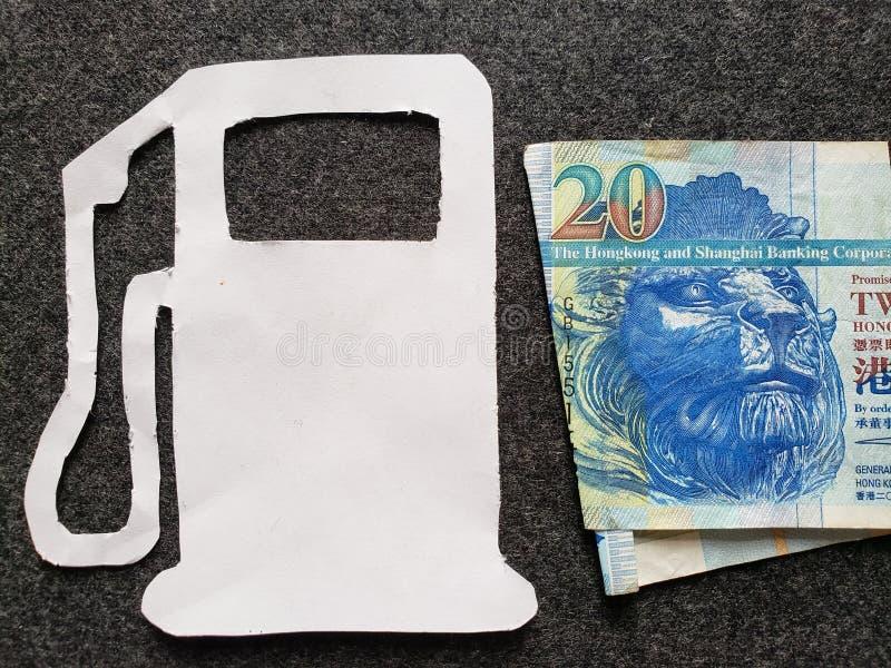 cijfer van benzinepomp in wit en een Hong Kong-bankbiljet van twintig dollars royalty-vrije stock foto