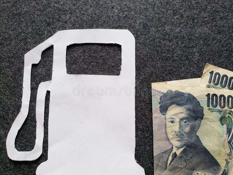 cijfer van benzinepomp in wit en een Japans bankbiljet van 1000 Yen stock fotografie