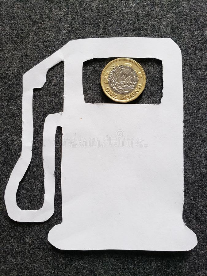 cijfer van benzinepomp in wit en een muntstuk van één echt pond royalty-vrije stock foto's