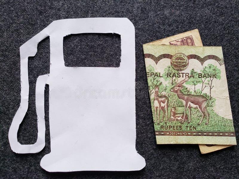 cijfer van benzinepomp in wit en een Nepalees bankbiljet van tien Roepies royalty-vrije stock foto