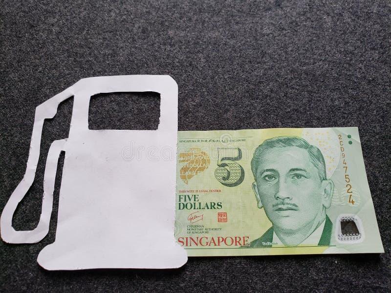 cijfer van benzinepomp in wit en een singaporean bankbiljet van vijf dollars stock fotografie
