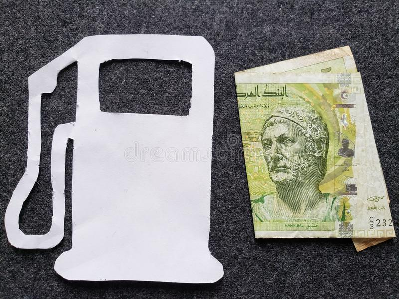 cijfer van benzinepomp in wit en een Tunesisch bankbiljet van vijf dinars royalty-vrije stock afbeelding