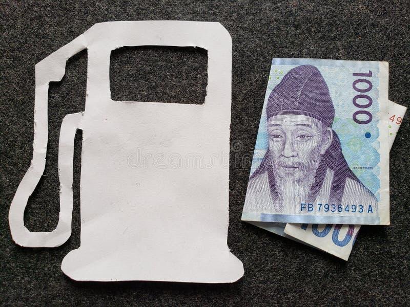 cijfer van benzinepomp in wit en een Zuidkoreaans bankbiljet van gewonnen 1000 stock foto