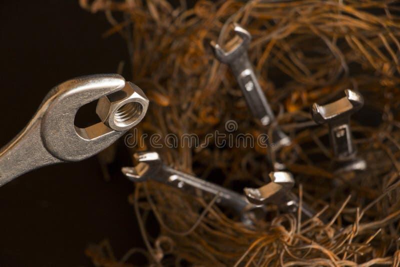 Cijfer van een vogelsnest met staaldraden en moersleutels wordt gemaakt die Het grootst van hen simuleert het zijn de moeder die  stock afbeeldingen