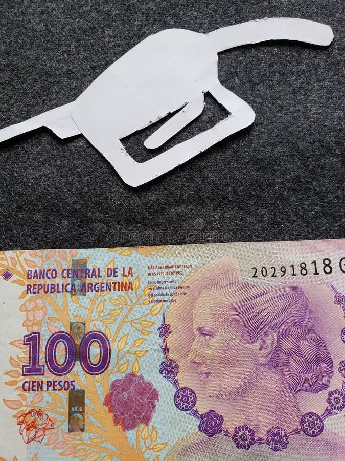 cijfer van het pistool van een benzinebom in wit en een Argentijns bankbiljet van 100 peso's royalty-vrije stock fotografie