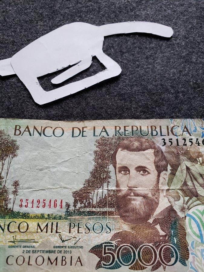 cijfer van het pistool van een benzinebom in wit en Columbiaans bankbiljet van 5000 peso's royalty-vrije stock foto
