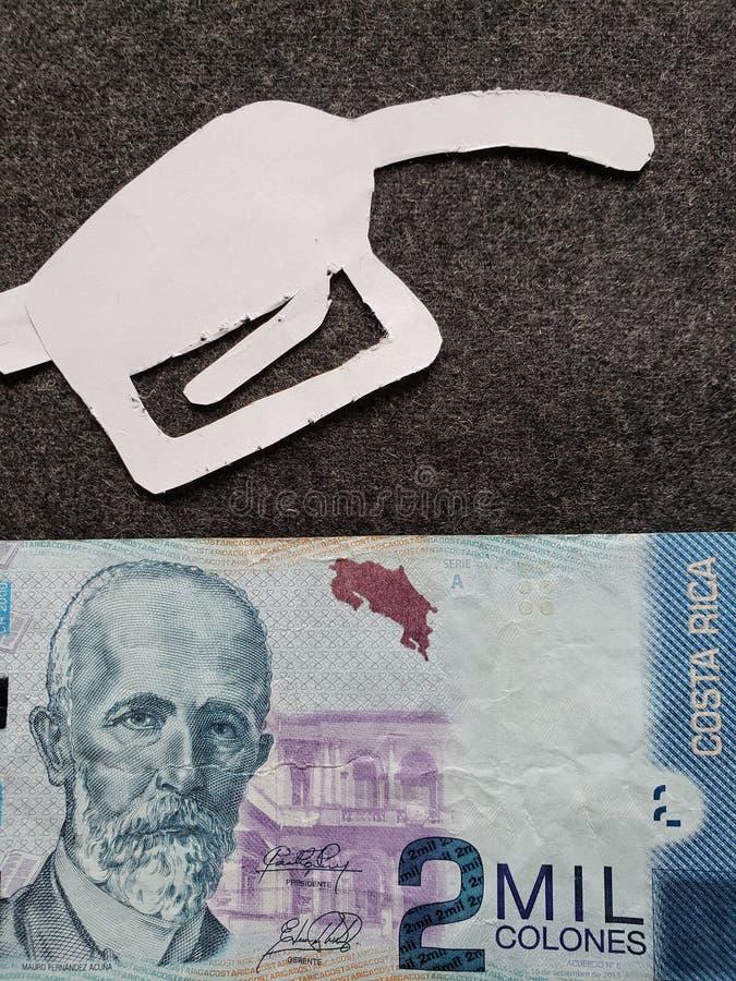 cijfer van het pistool van een benzinebom in wit en een Costa Rican-bankbiljet van colones van 2000 stock foto's