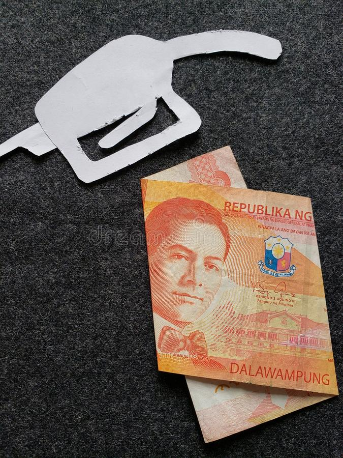 cijfer van het pistool van een benzinebom in wit en een Filippijns bankbiljet van twintig peso's stock afbeelding