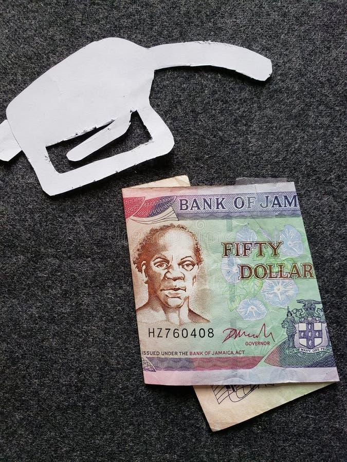 cijfer van het pistool van een benzinebom in wit en een Jamaicaans bankbiljet van vijftig dollars royalty-vrije stock foto's