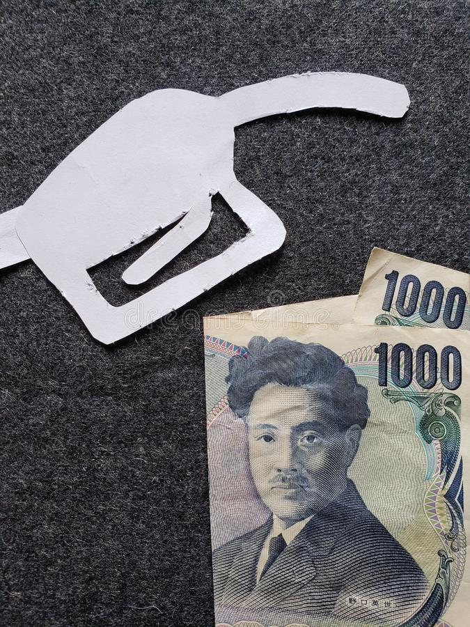 cijfer van het pistool van een benzinebom in wit en Japans bankbiljet van 1000 Yen stock foto