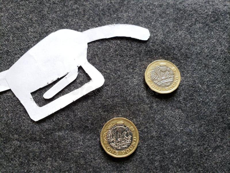 cijfer van het pistool van een benzinebom in wit en muntstukken van één echt pond stock foto
