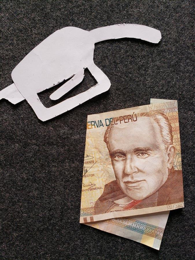 cijfer van het pistool van een benzinebom in wit en een Peruviaans bankbiljet van twintig zolen royalty-vrije stock foto
