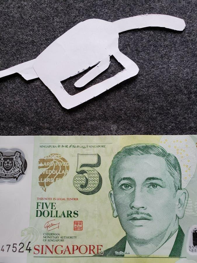 cijfer van het pistool van een benzinebom in wit en een singaporean bankbiljet van vijf dollars stock fotografie