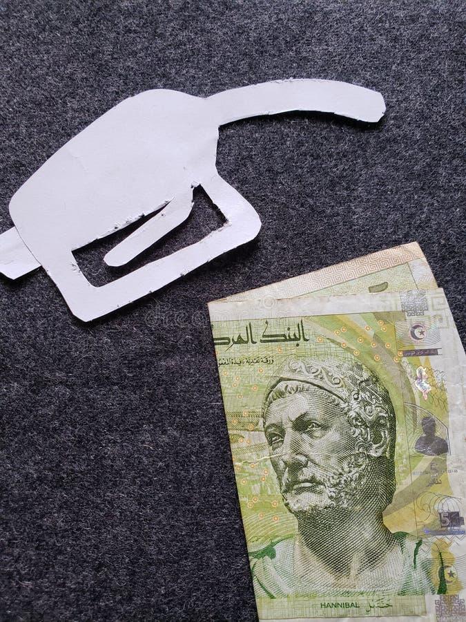 cijfer van het pistool van een benzinebom in wit en een Tunesisch bankbiljet van vijf dinars royalty-vrije stock afbeelding