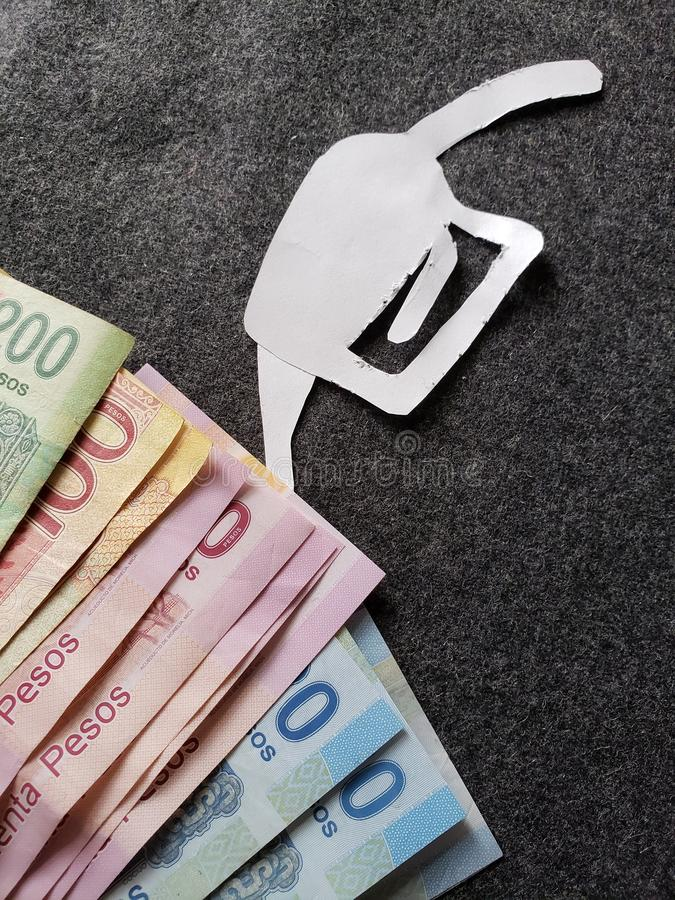 cijfer van het pistool van een benzinebom in Witboek en Mexicaanse bankbiljetten van verschillende benamingen stock foto