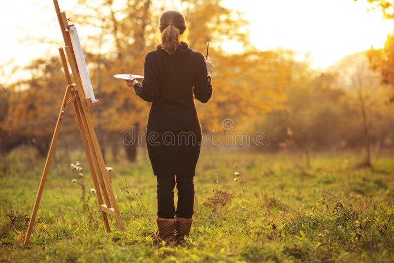 Cijfer van jonge vrouwenkunstenaar die een beeld op de schildersezel, meisje schilderen die de herfst van aard die en werken geni stock afbeelding