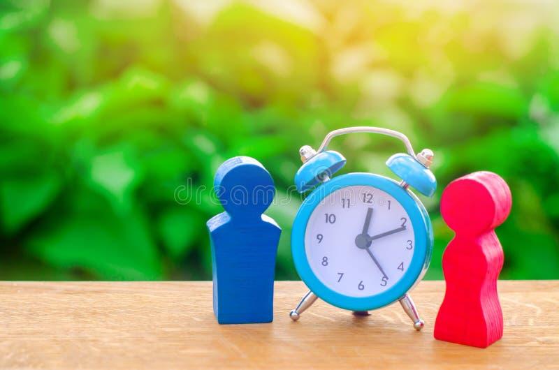 Cijfers van een man en een vrouw die zich dichtbij de wekker bevinden Concept vergadering of datum Het verband tussen een man en  stock foto