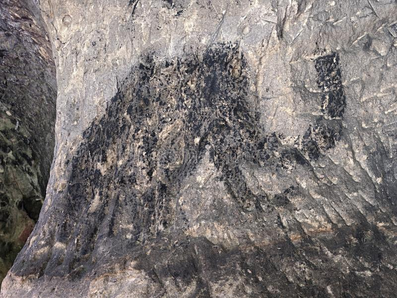 Cildren art in sandstone cave. Black carbon mammoth paint. Abstract children art in sandstone cave. Black carbon mammoth paint of human hunting on sandstone wall royalty free stock images