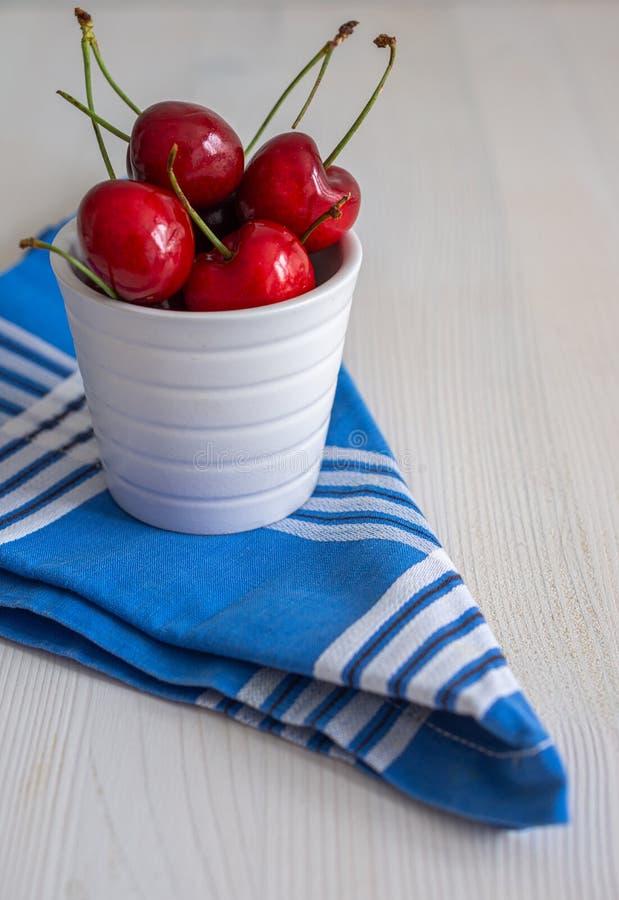 Ciliege in ciotola bianca sul tovagliolo a quadretti blu e nel fondo di legno bianco fotografia stock