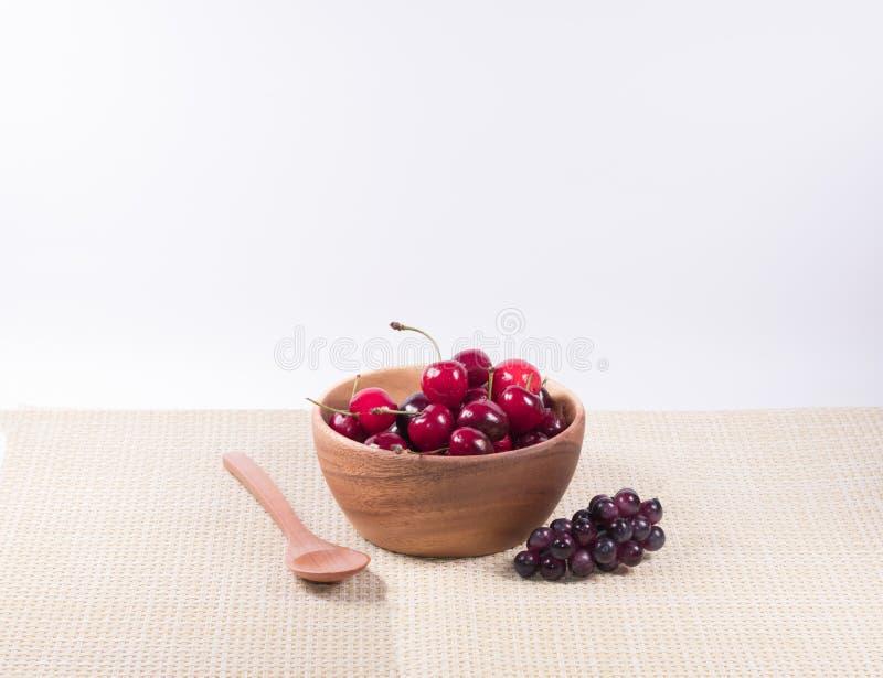 Ciliege in ciotola di legno e cucchiaio di legno, uva scura, fiore immagine stock