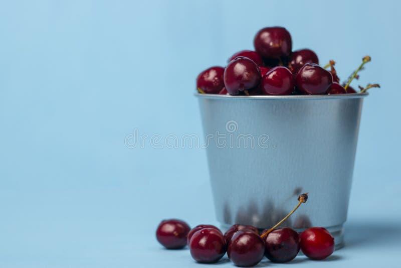 Ciliegia dolce e matura in un piccolo secchio di alluminio su un fondo blu concetto delle bacche di estate con lo spazio della co fotografie stock libere da diritti