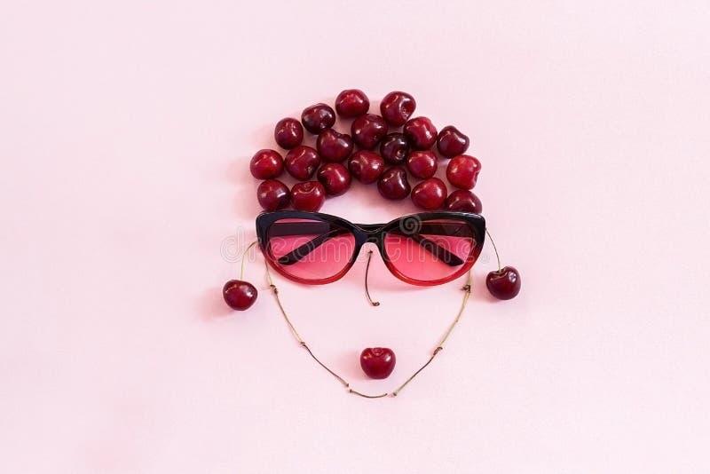 Ciliegia rossa presentata nell'immagine della donna in occhiali da sole con le labbra su fondo rosa Giovent? di concetto, bellezz immagini stock libere da diritti