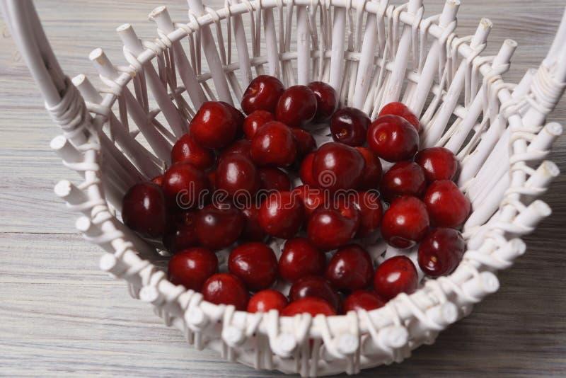 Ciliegie rosse in un canestro bianco su una tavola di legno bianca immagini stock libere da diritti