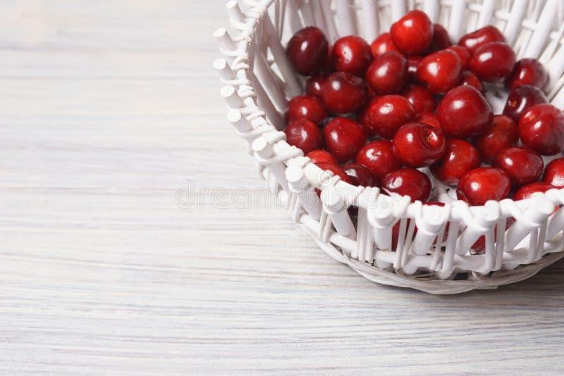 Ciliegie rosse in un canestro bianco su una tavola di legno bianca fotografia stock