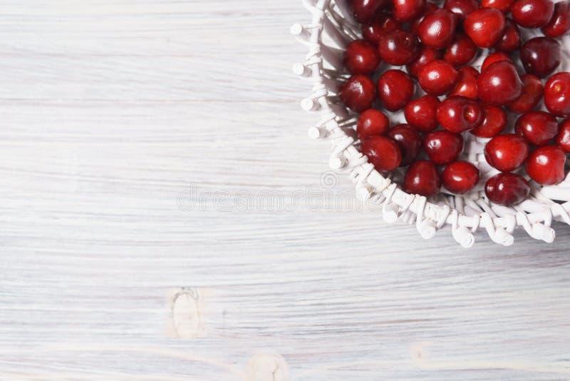 Ciliegie rosse in un canestro bianco su una tavola di legno bianca fotografie stock