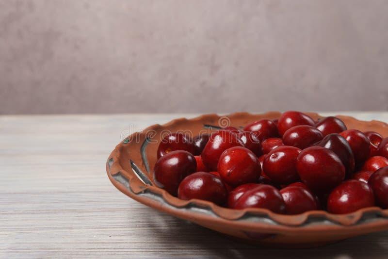 Ciliegie rosse in un piatto dell'argilla su una tavola di legno bianca fotografie stock