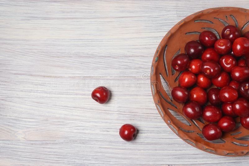 Ciliegie rosse in un piatto dell'argilla su una tavola di legno bianca immagine stock