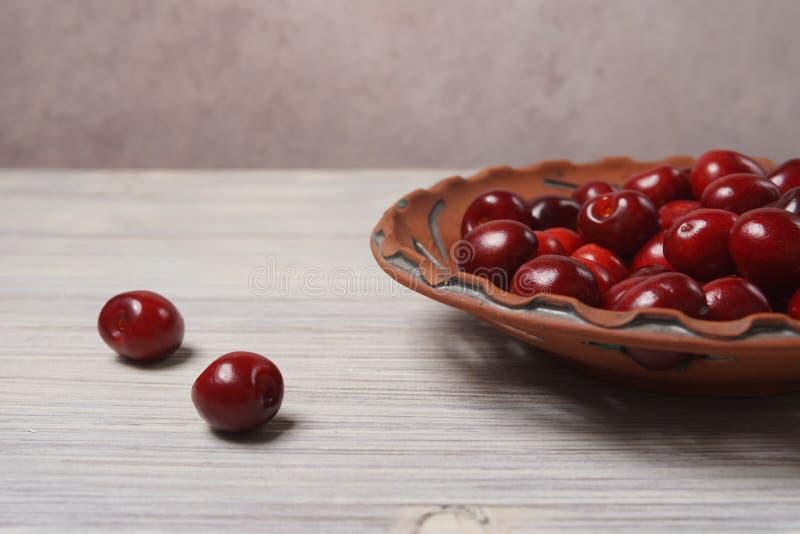 Ciliegie rosse in un piatto dell'argilla su una tavola di legno bianca immagine stock libera da diritti