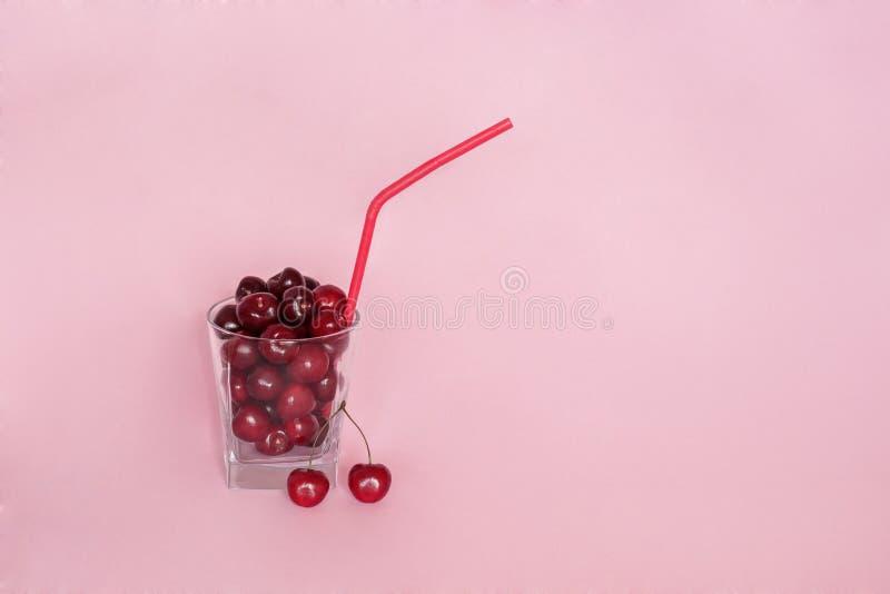 Ciliegie in vetro con la paglia del cocktail, su fondo rosa immagine stock libera da diritti