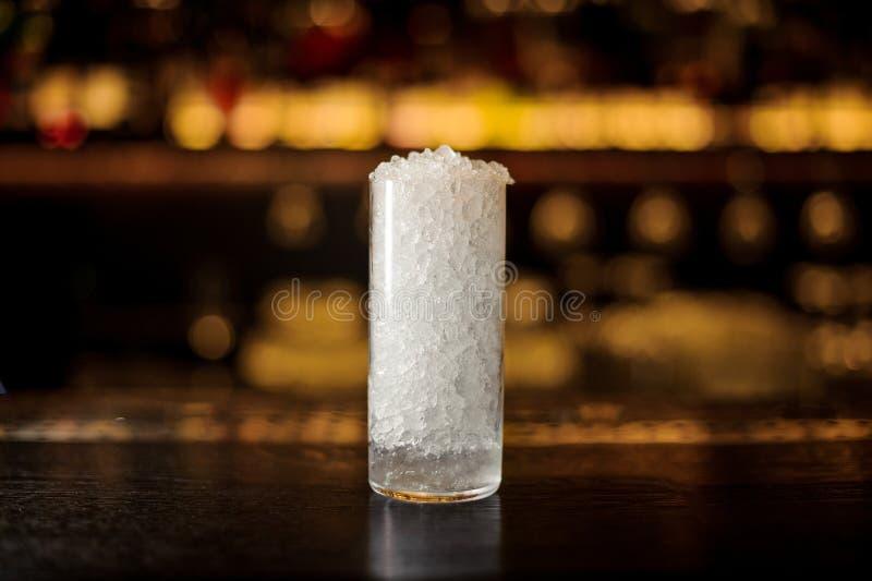 Cilindrisch cocktailglas van verpletterd ijs die zich op de bartribune bevinden royalty-vrije stock afbeeldingen
