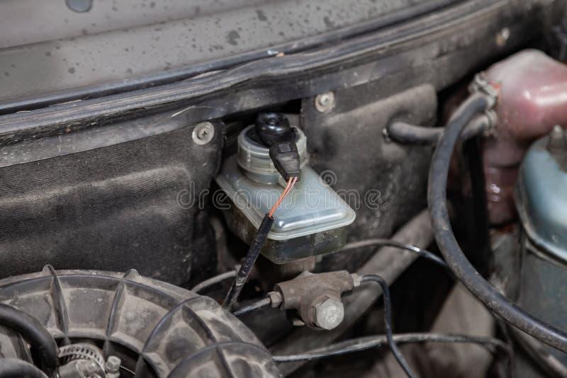 Cilindro de freno del tanque manchado con aceite con un sensor llano y los electricistas de los alambres en el compartimiento del foto de archivo
