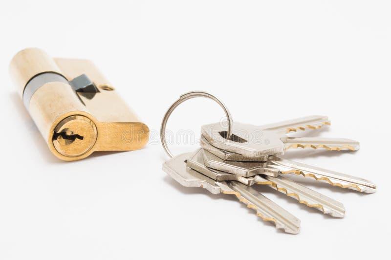 Cilindro de la cerradura de puerta con el manojo de llaves en el fondo blanco fotografía de archivo libre de regalías